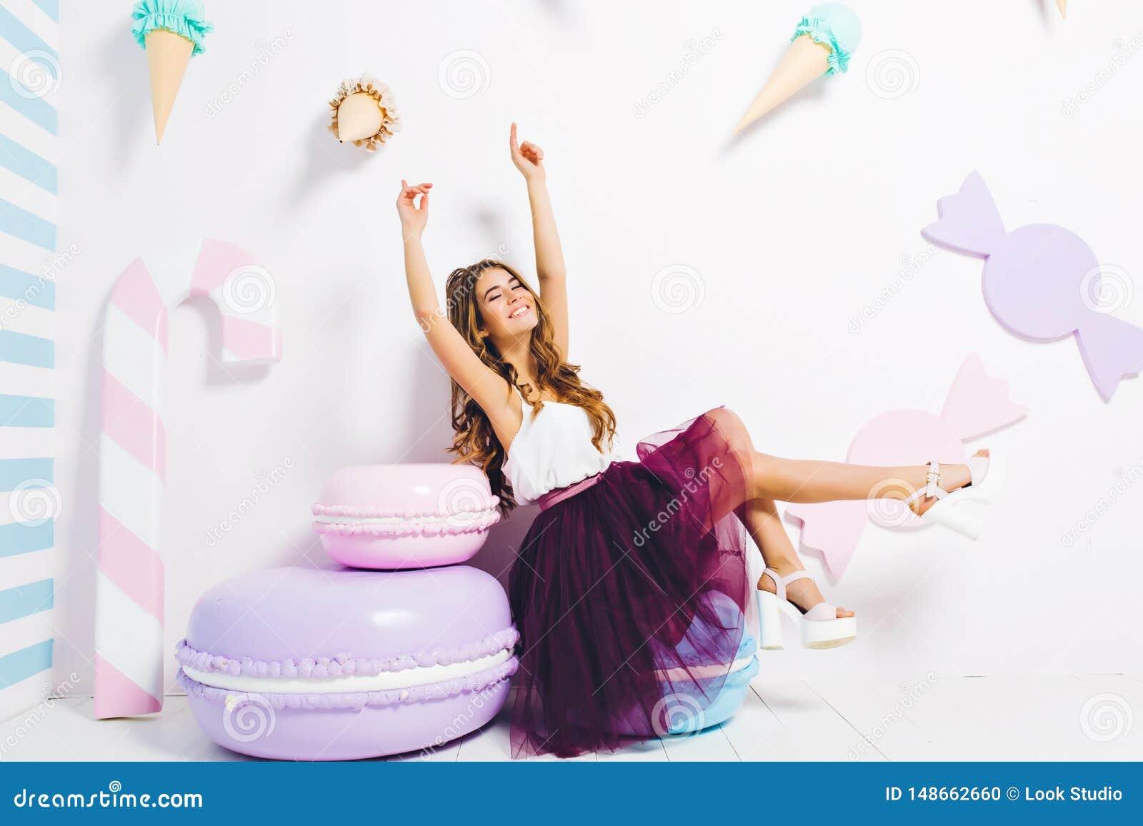 Romantisch meisje in in witte gehielde schoenen die pret op haar verjaardagspartij hebben, die op stuk speelgoed koekje zitten di
