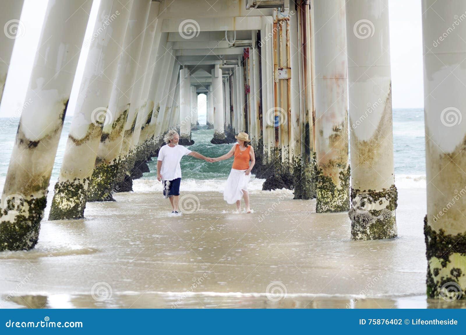 Romantisch ouder rijp man & vrouwenpaar onbezorgd op de tijd van de strandzomer