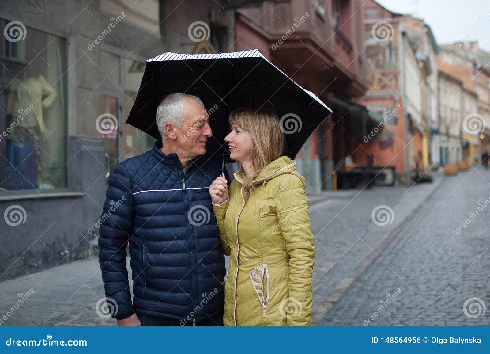 Romantisch paar die met leeftijdsverschil aan elkaar met geluk en het glimlachen status onder hun paraplu kijken