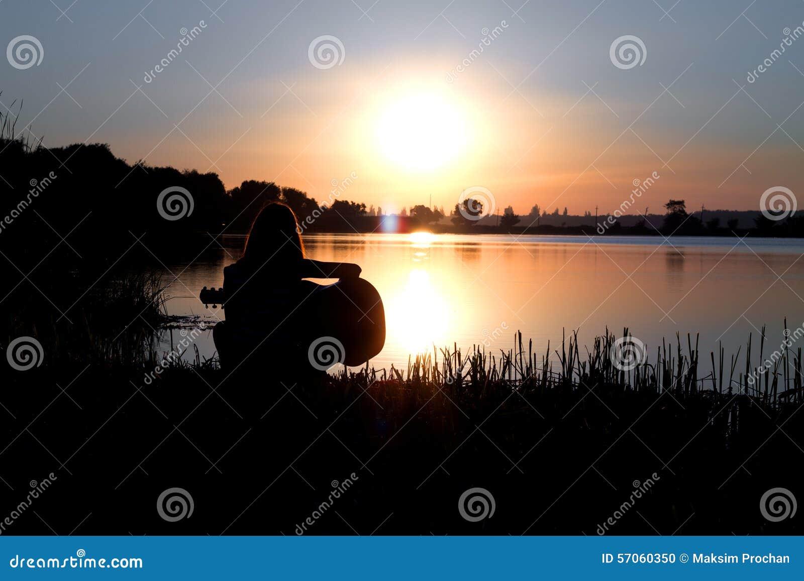Romantisch silhouet van het meisje door de rivier het spelen gitaar