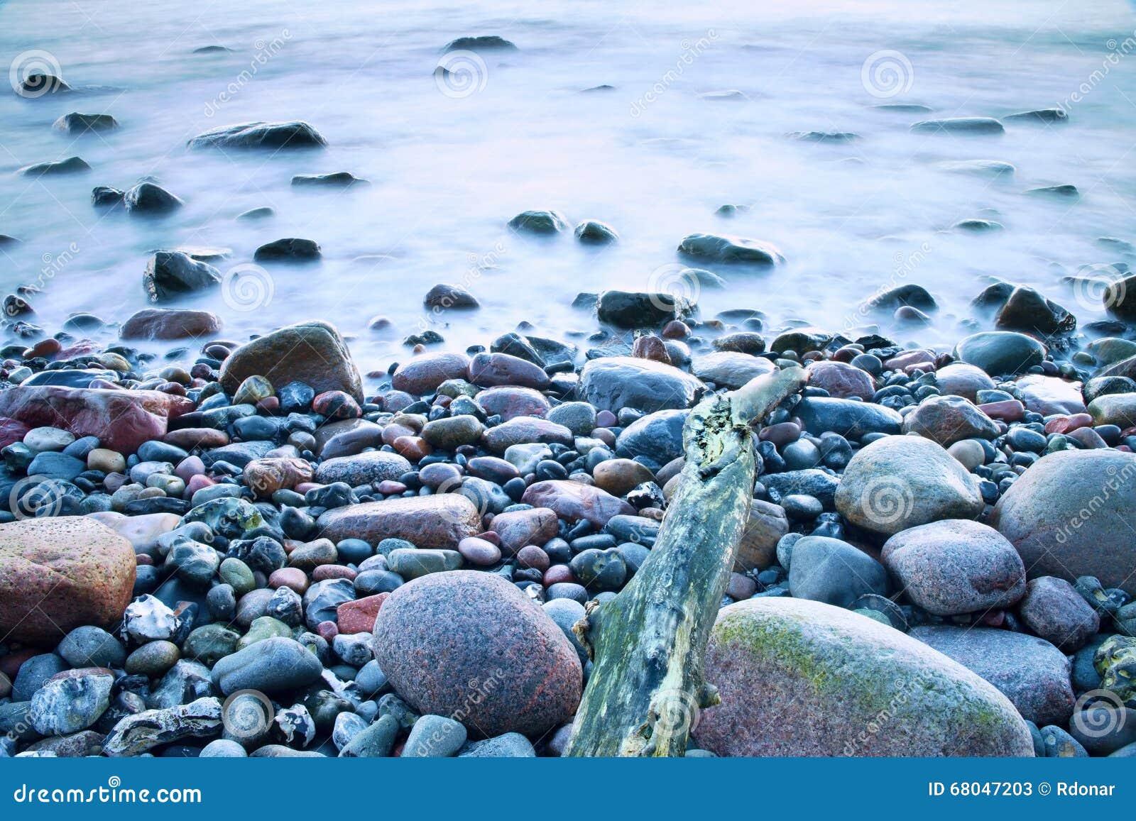 Romantische atmosfeer in vreedzame ochtend op zee grote keien die uit van vlotte golvende - Romantische kameratmosfeer ...