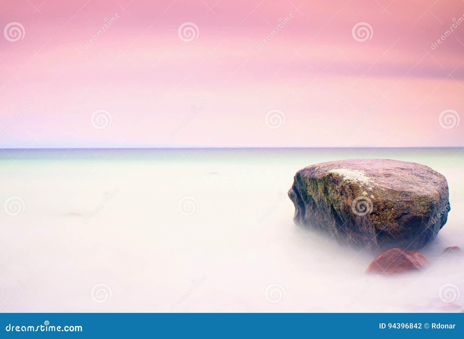 Romantische Atmosphäre am ruhigen Morgen in Meer Große Flusssteine, die heraus vom glatten gewellten Meer haften Rosa Horizont