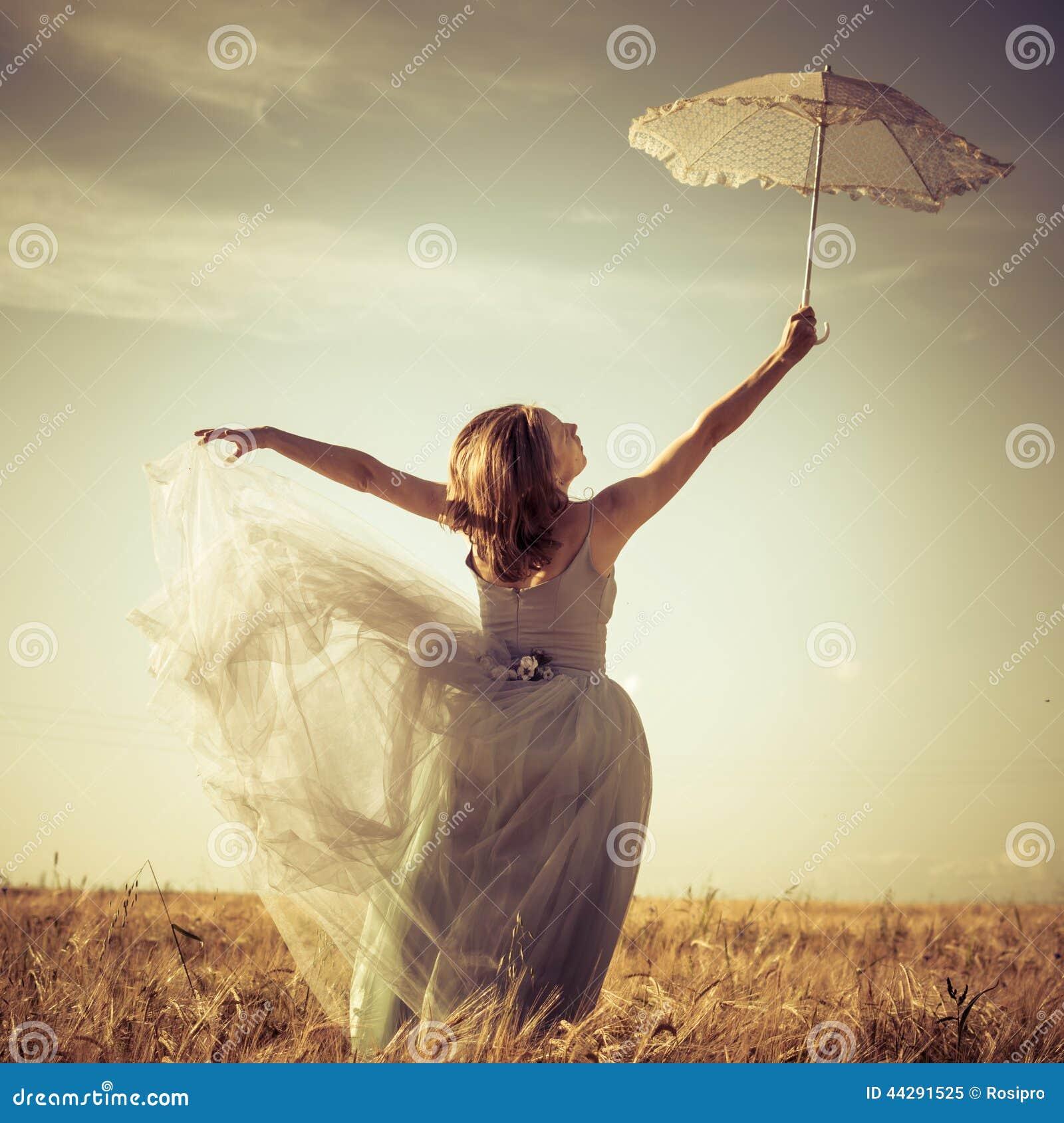Romantische de zomer in openlucht fee: mooie blonde jonge vrouw die pret hebben die lange lichte kleding dragen en witte kantpara