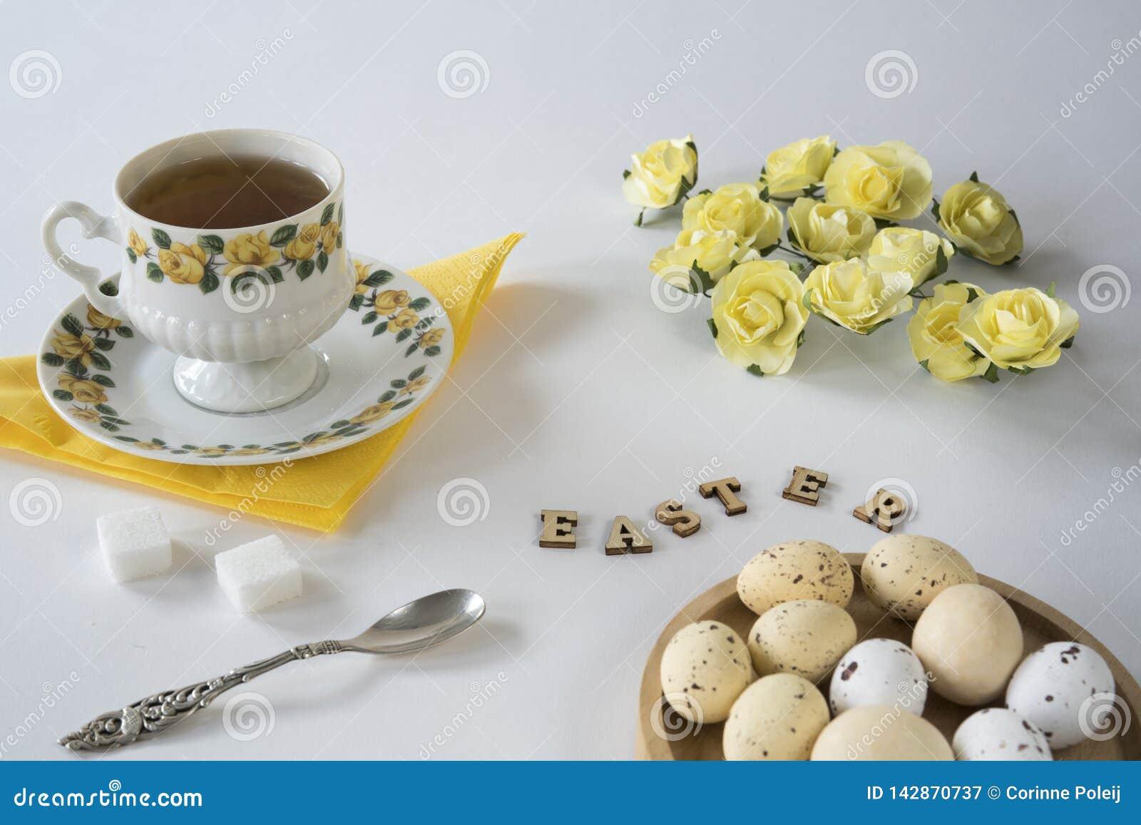 Romantische gelbe Ostern-Szene mit Tee, Ostereiern, Löffel und Rosen