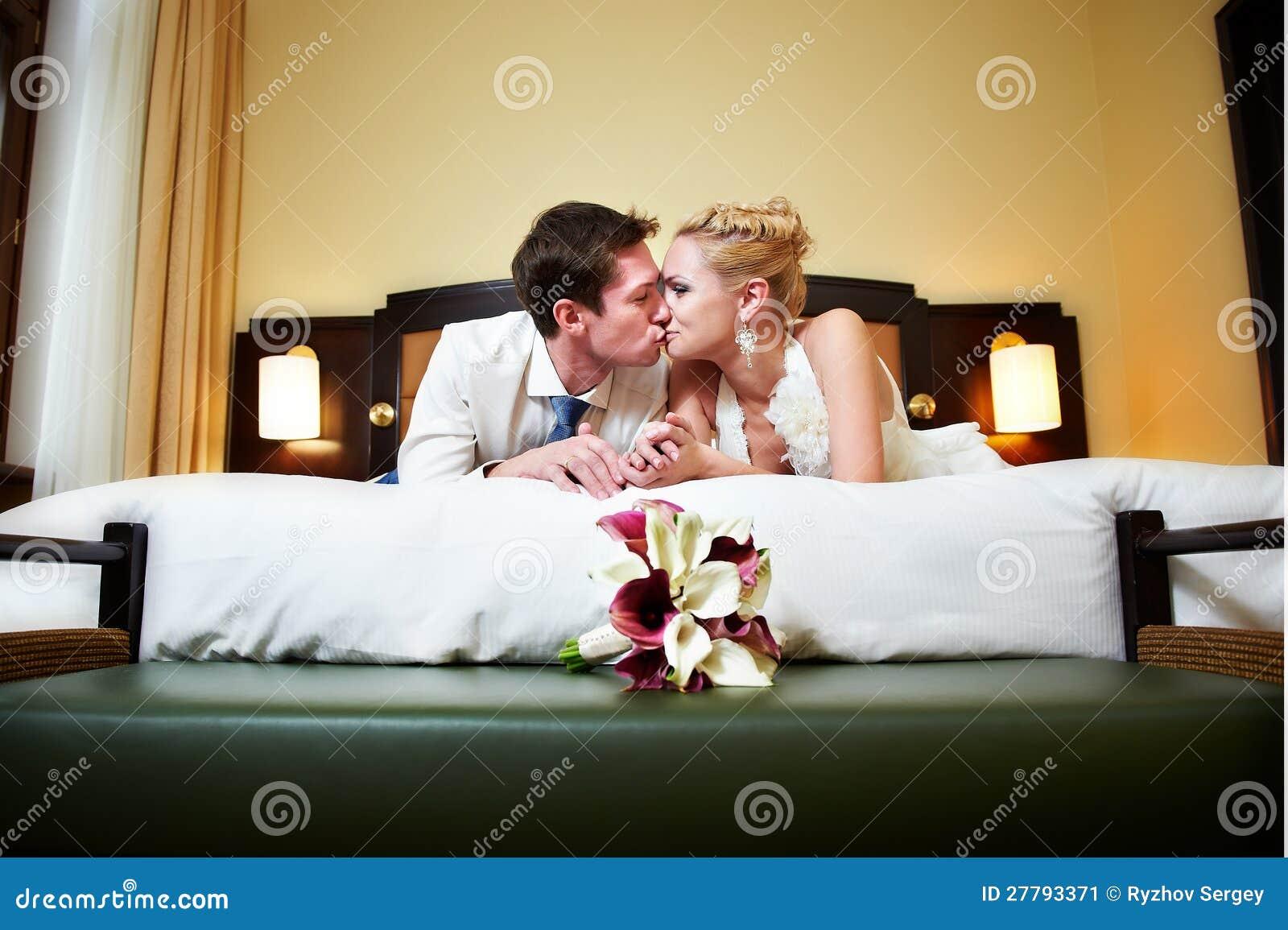 Romantische kus gelukkige bruid en bruidegom in slaapkamer stock ...