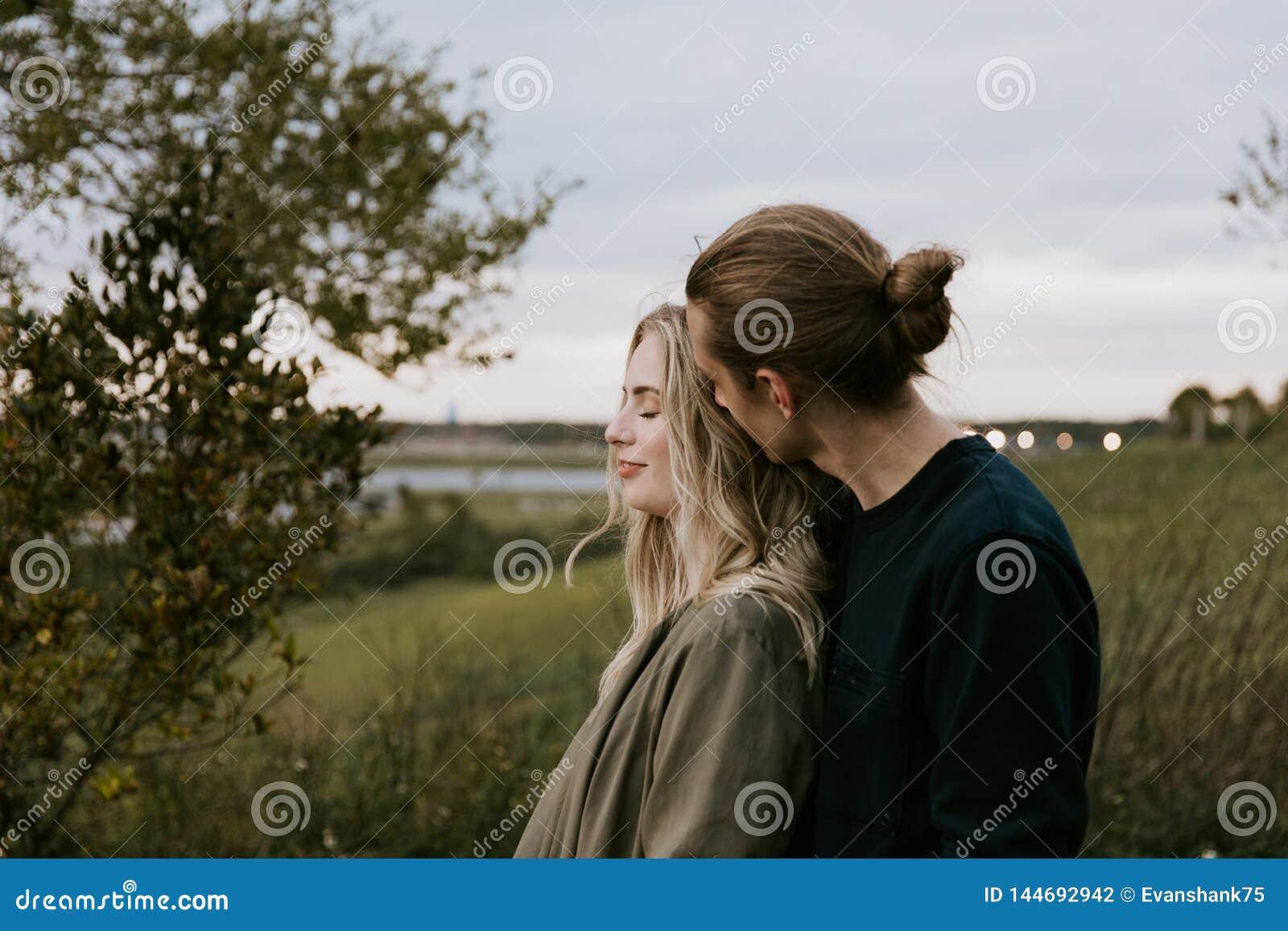 Romantische und liebevolle junge erwachsene Paare am Park, der Natur und den Horizont nach Porträt-Bildern betrachtet