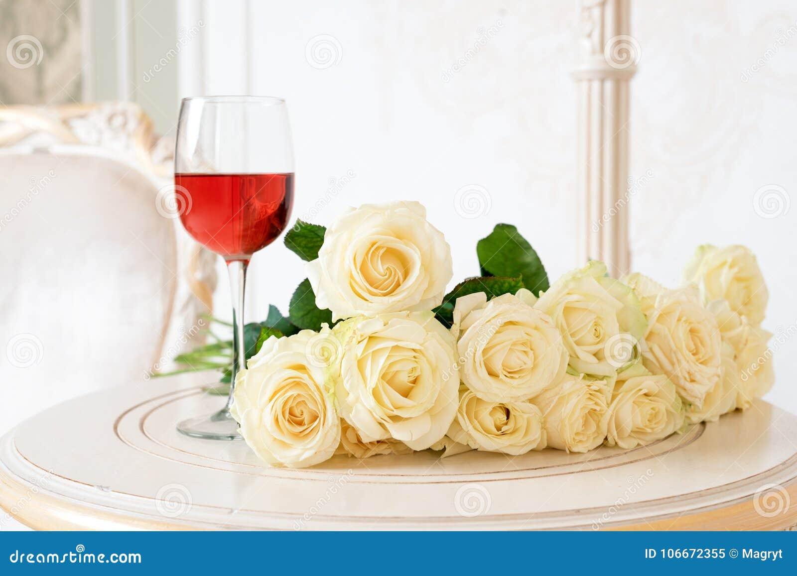 Romantische vakantiesamenstelling met wijnglas en rozen voor Valentijnskaartendag Liefde, gift en de lentevakantieachtergrond