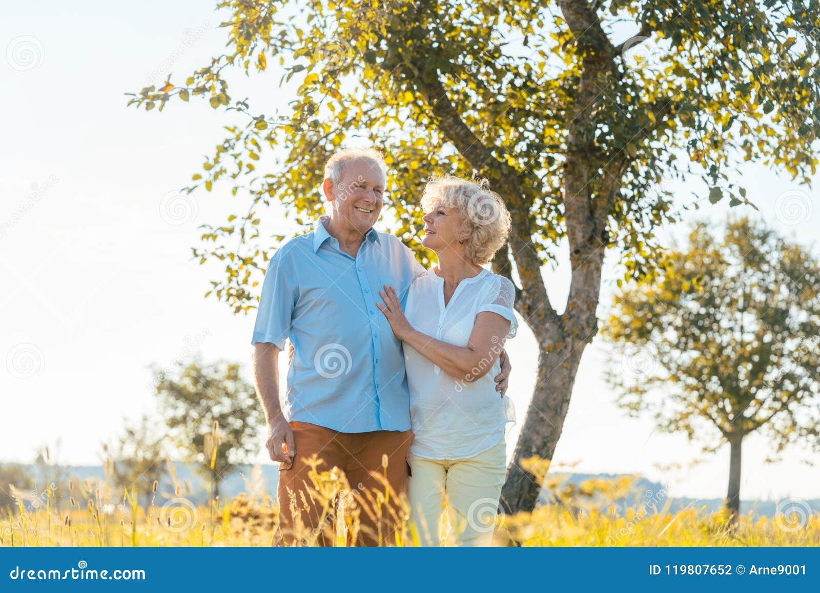 Romantisches älteres Paarhändchenhalten beim in die Landschaft zusammen gehen