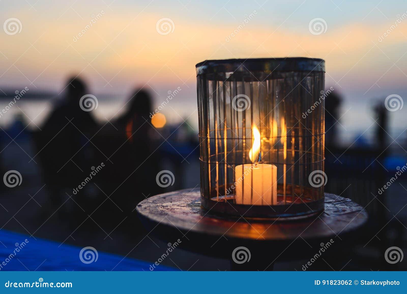 Romantisches Abendessen in einem Café auf dem Ozean durch Sonnenuntergang Eine Kerze brennt auf einer Tabelle für Gäste in einem