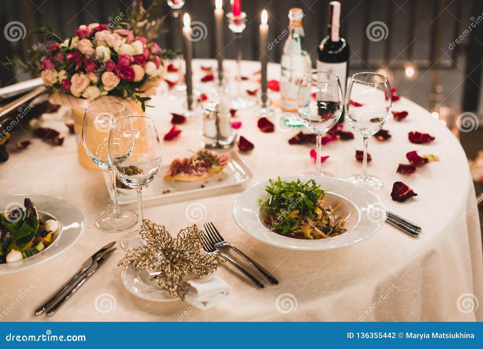 Romantisches Gedeck mit Wein, schöne Blumen im Kasten, leere Gläser, stieg Blumenblätter und Kerzen