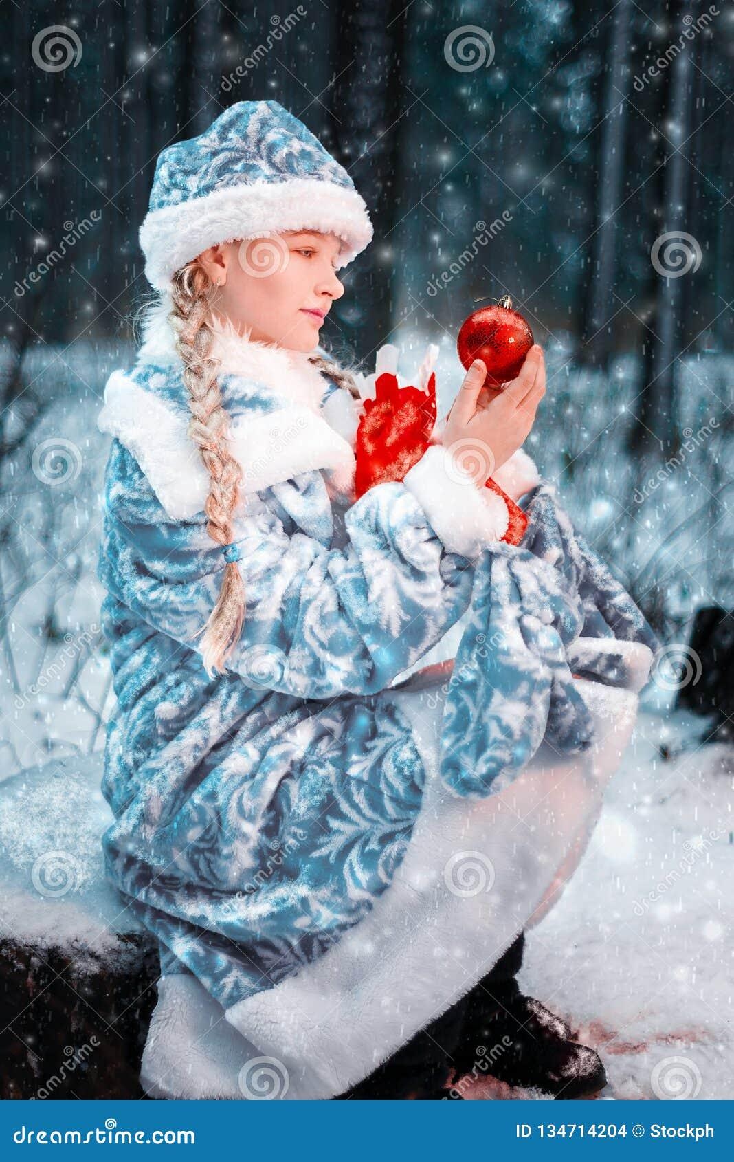 Romantisches Schnee-Mädchen in einem festlichen Kostüm wenig Mädchen hält das Spielzeug und eine Tasche des neuen Jahres mit Gesc