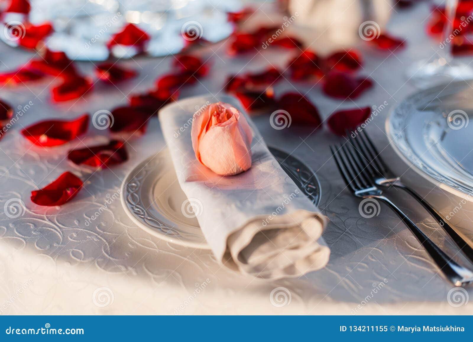 Romantisches Valentinstagabendessen gegründet mit den rosafarbenen Blumenblättern