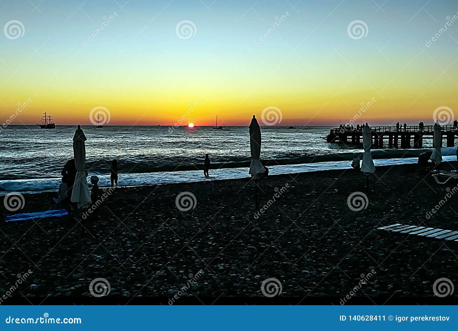 Romantisk afton och magisk solnedgång på stranden, konturer av folk