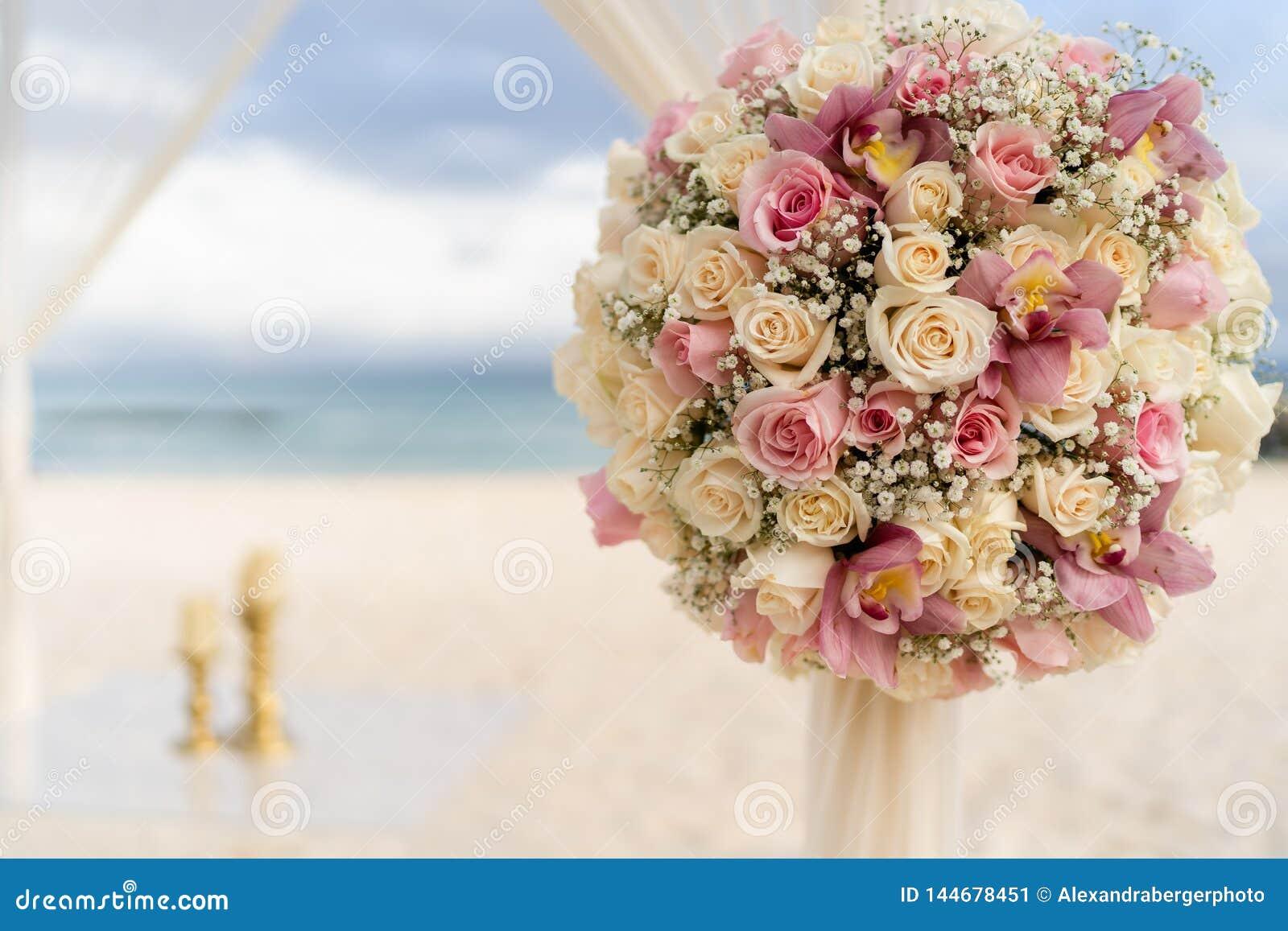 Romantisk garnering med blommor av ett strandbröllop på stranden med havet i bakgrunden