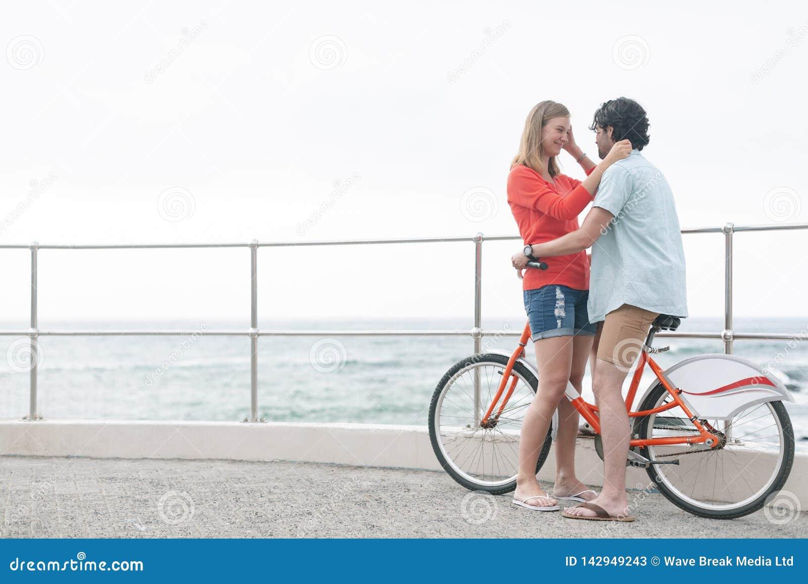 Romantiska Caucasian par som är pinsamma på cirkulering på stranden