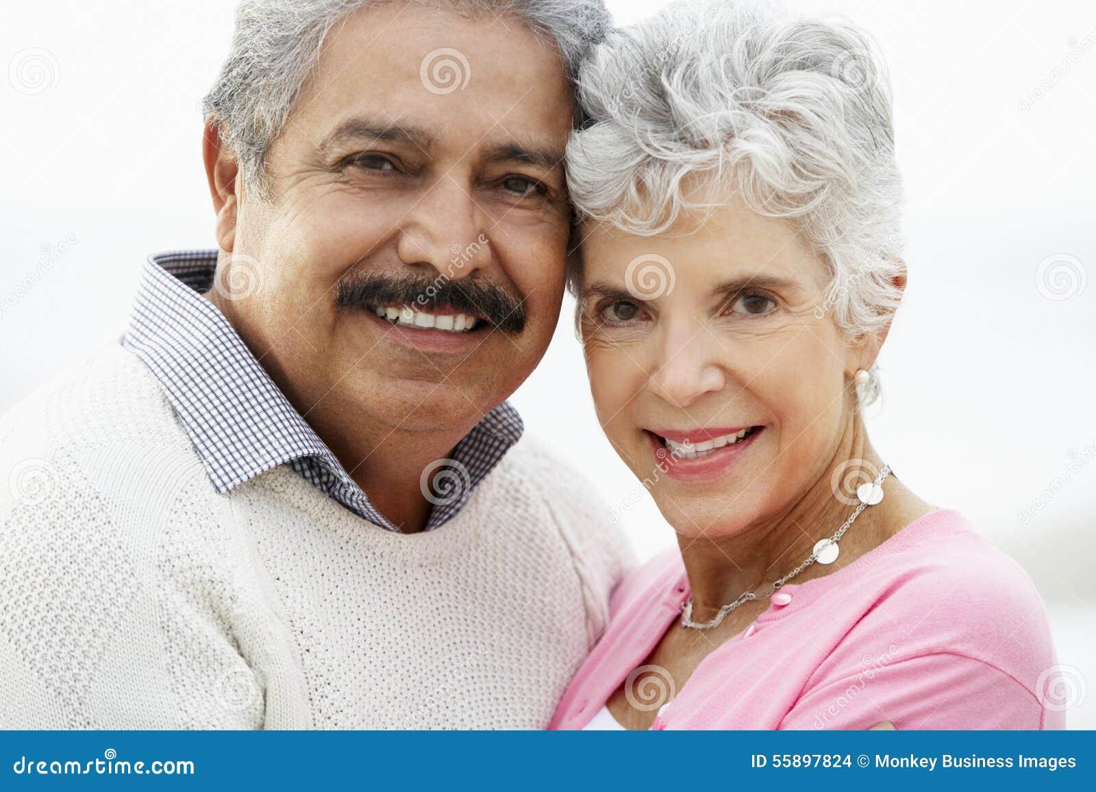 Romantiska höga par som kramar på strand