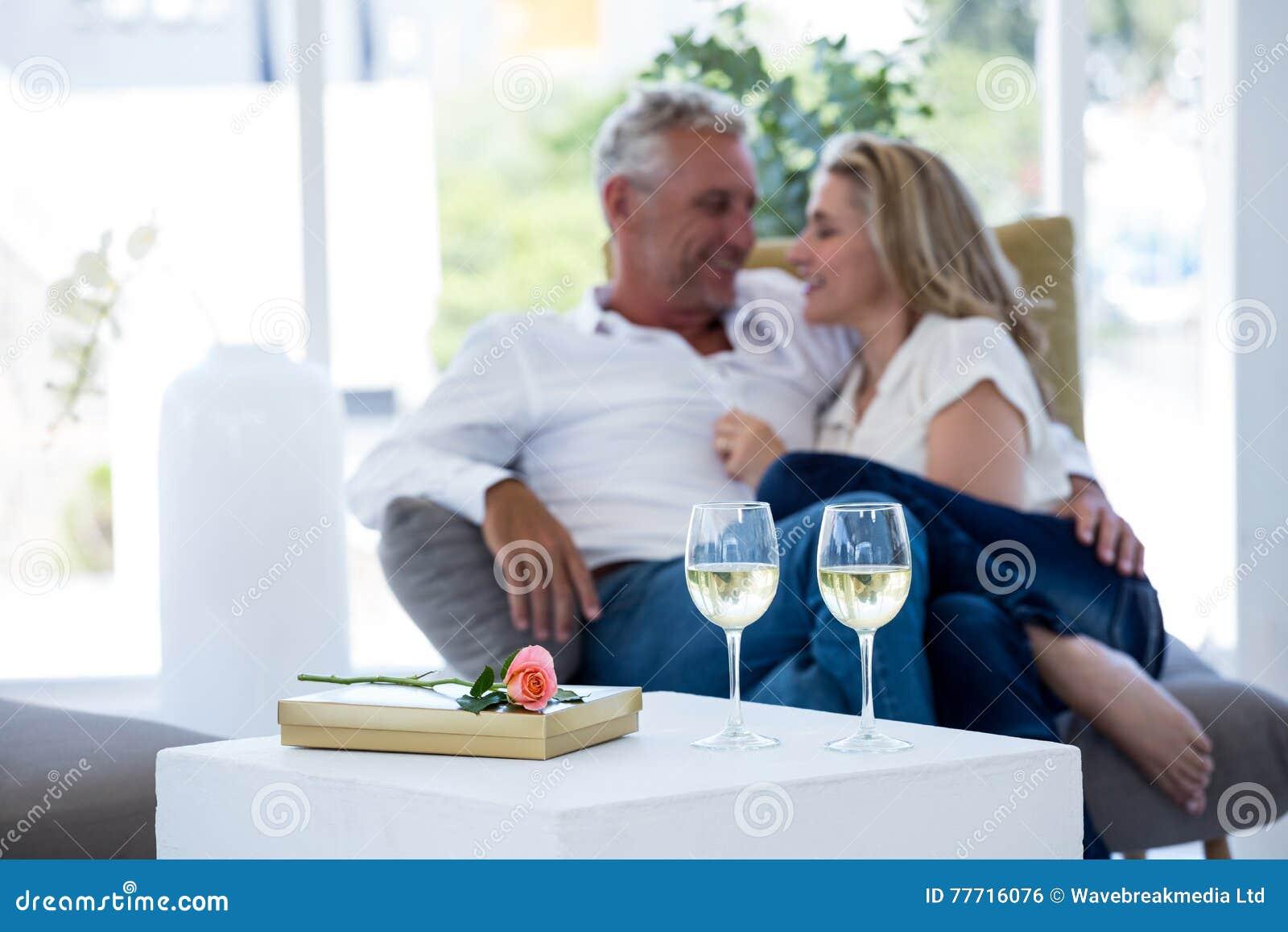 Romantiska par med exponeringsglas för vitt vin vid den rosa och gåvaasken på tabellen