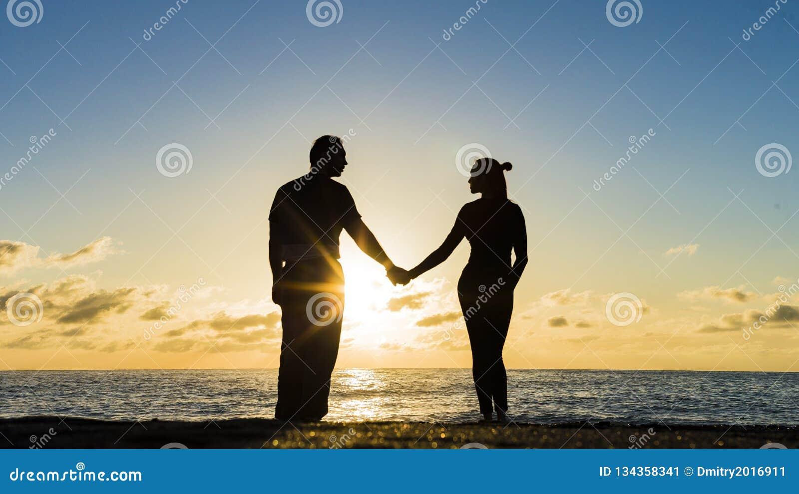 Romantiska par på stranden på den färgrika solnedgången på bakgrund
