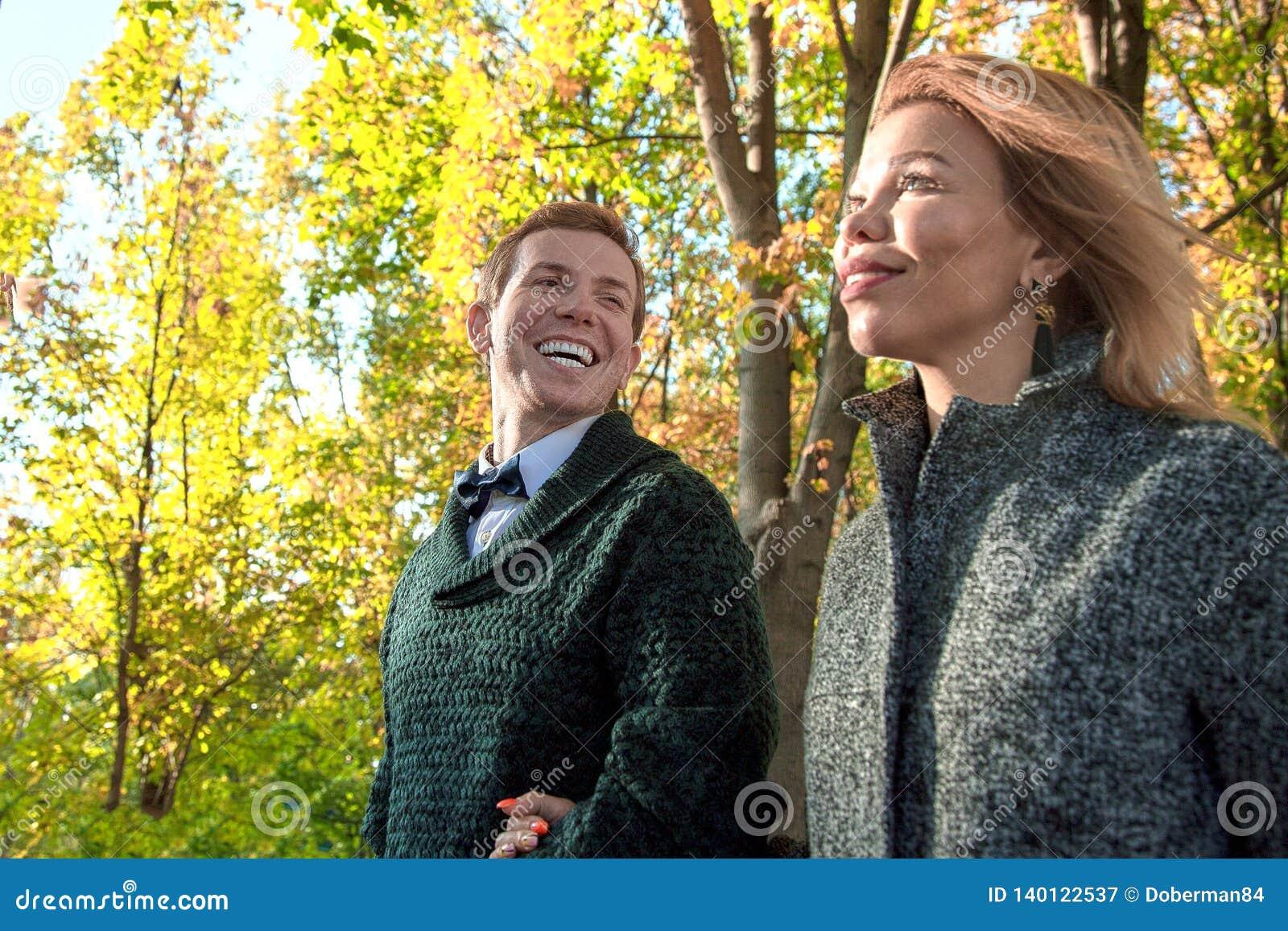 Romantiska par som kopplar av i höst, parkerar och att kela och att kyssa och att tycka om ny luft, den härliga naturen, trevligt