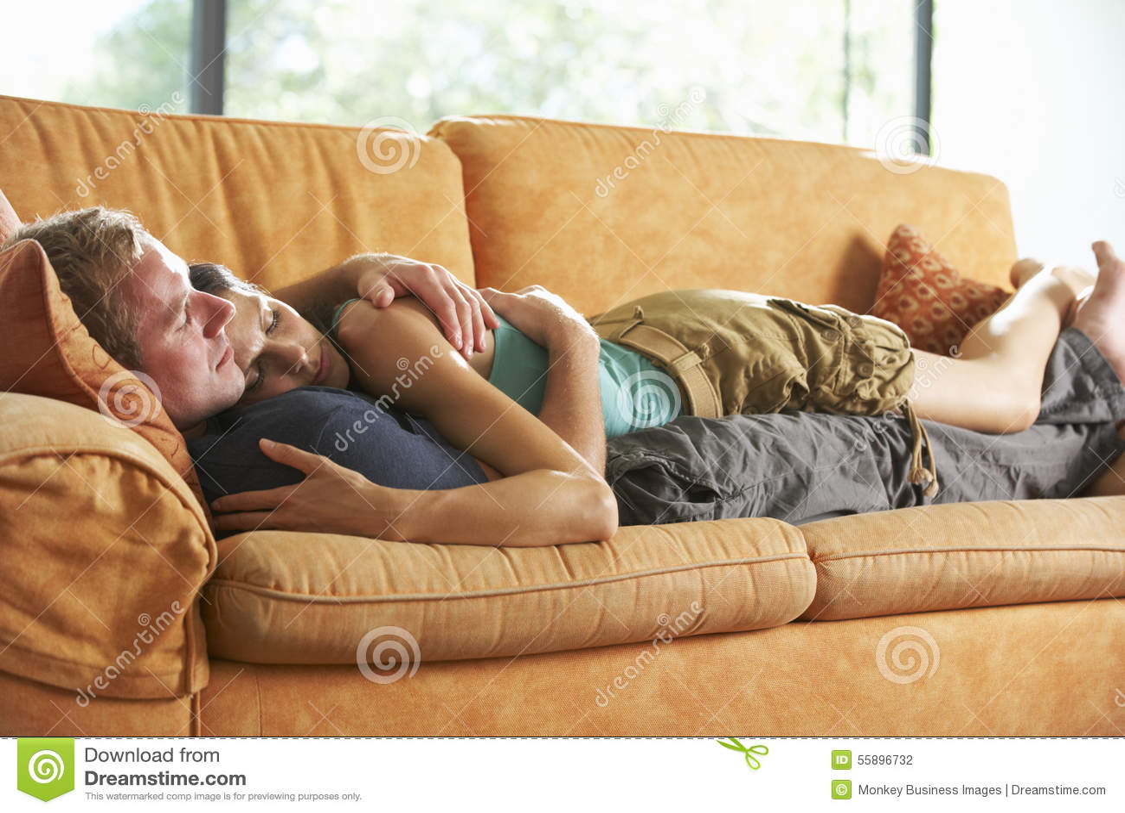 Romantiska par som ligger på Sofa At Home