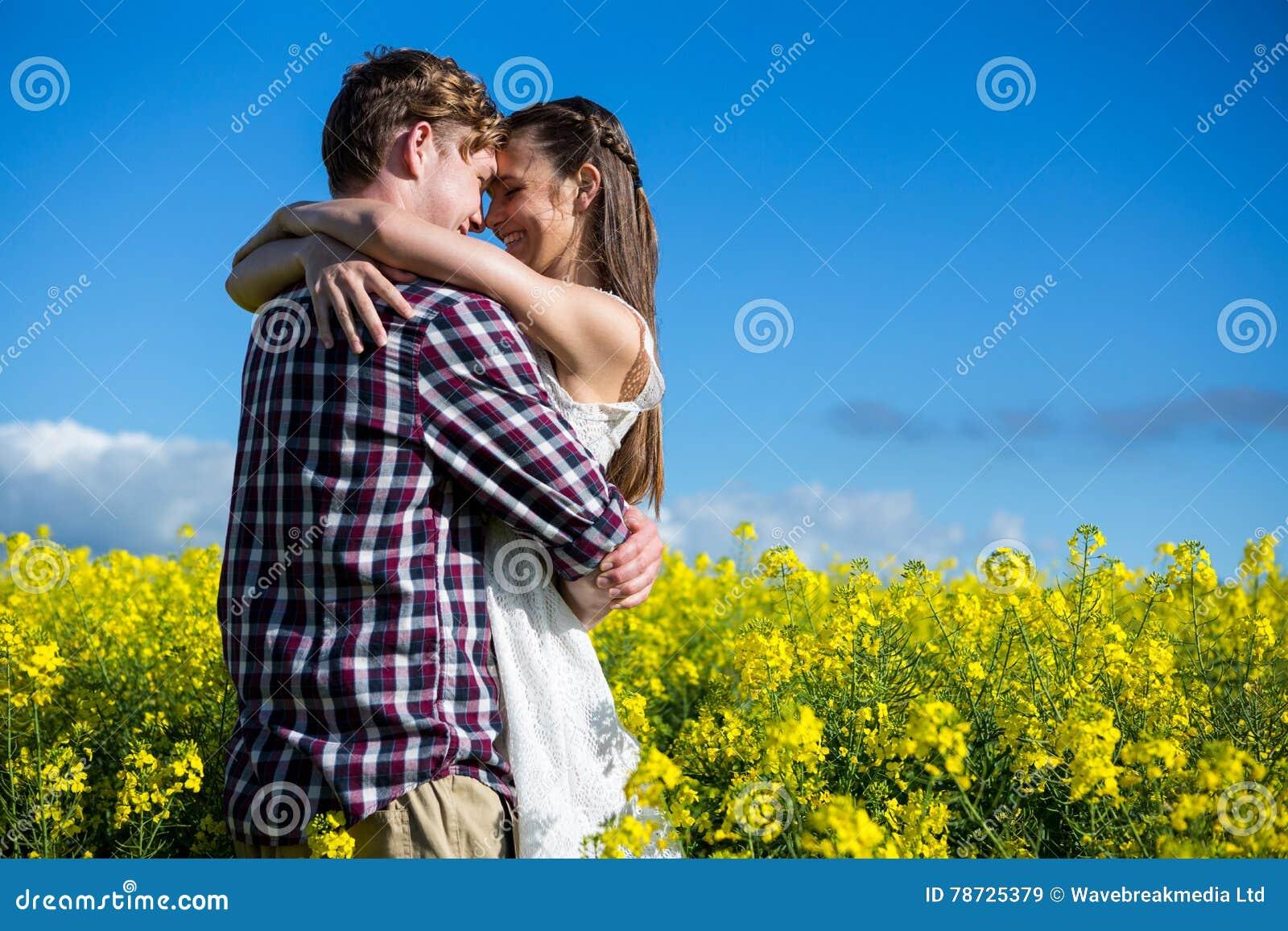 Romantiska par som omfamnar sig i senapsgult fält
