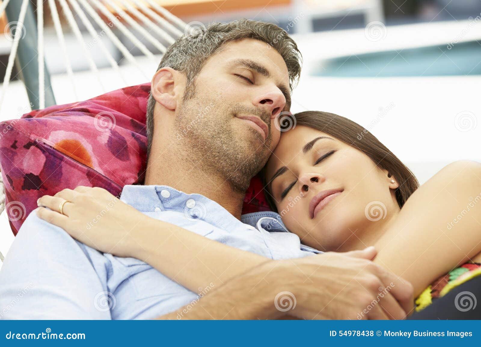 Romantiska par sovande i trädgårds- hängmatta tillsammans