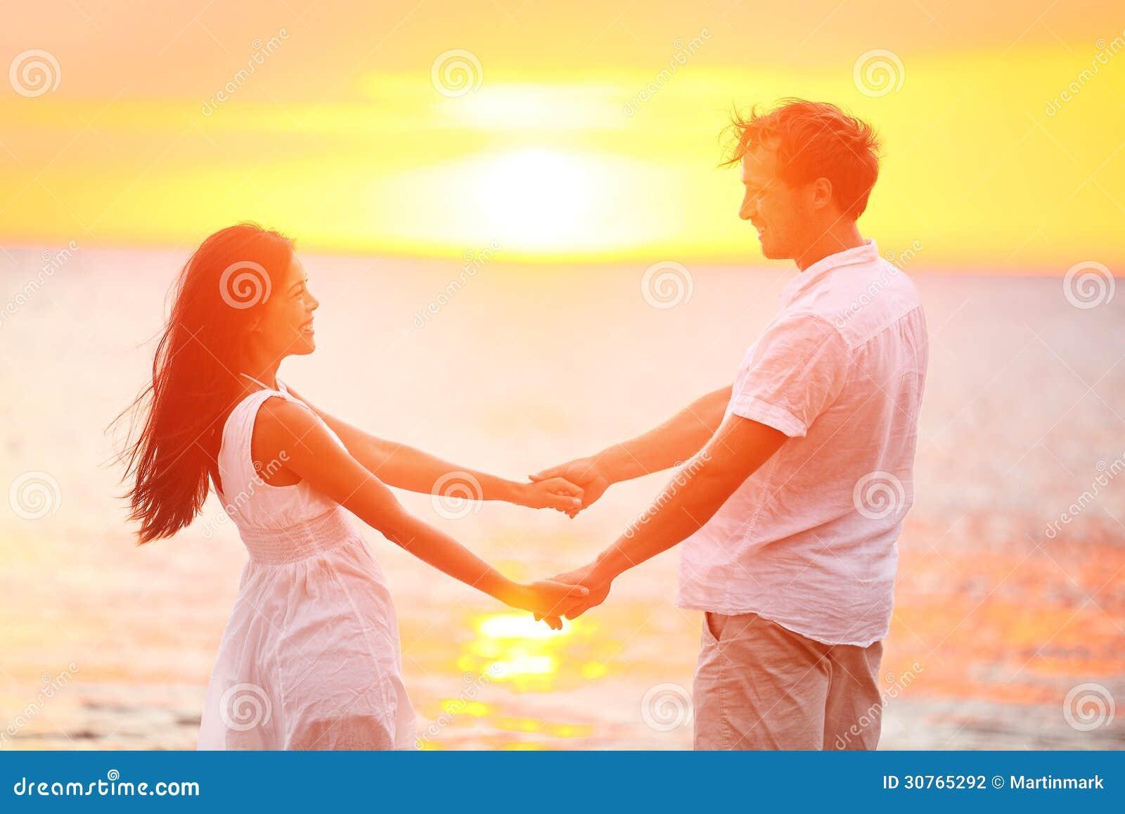 Romantiska parvänner som rymmer händer, strandsolnedgång