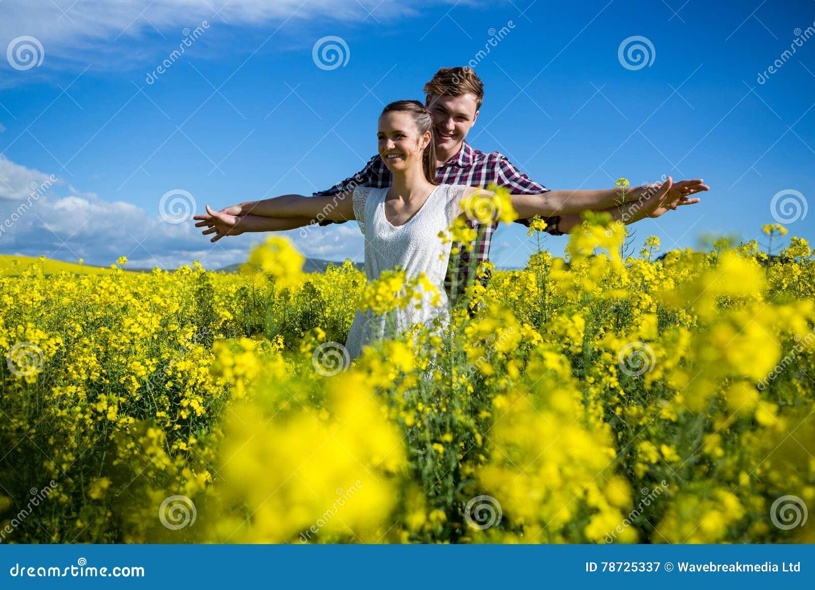 Romantiskt paranseende med armar som är utsträckta i senapsgult fält