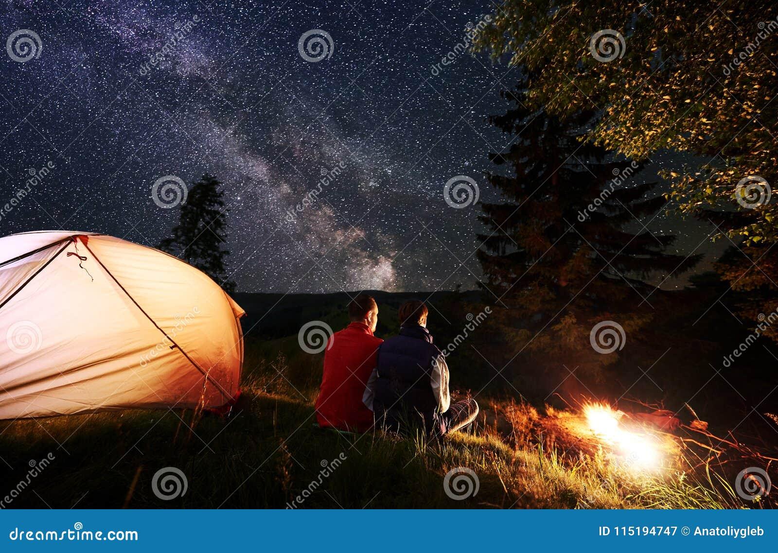 Romantiskt parsammanträde för bakre sikt i tältläger vid brand under natthimmel som beströs med stjärnor och den mjölkaktiga väge