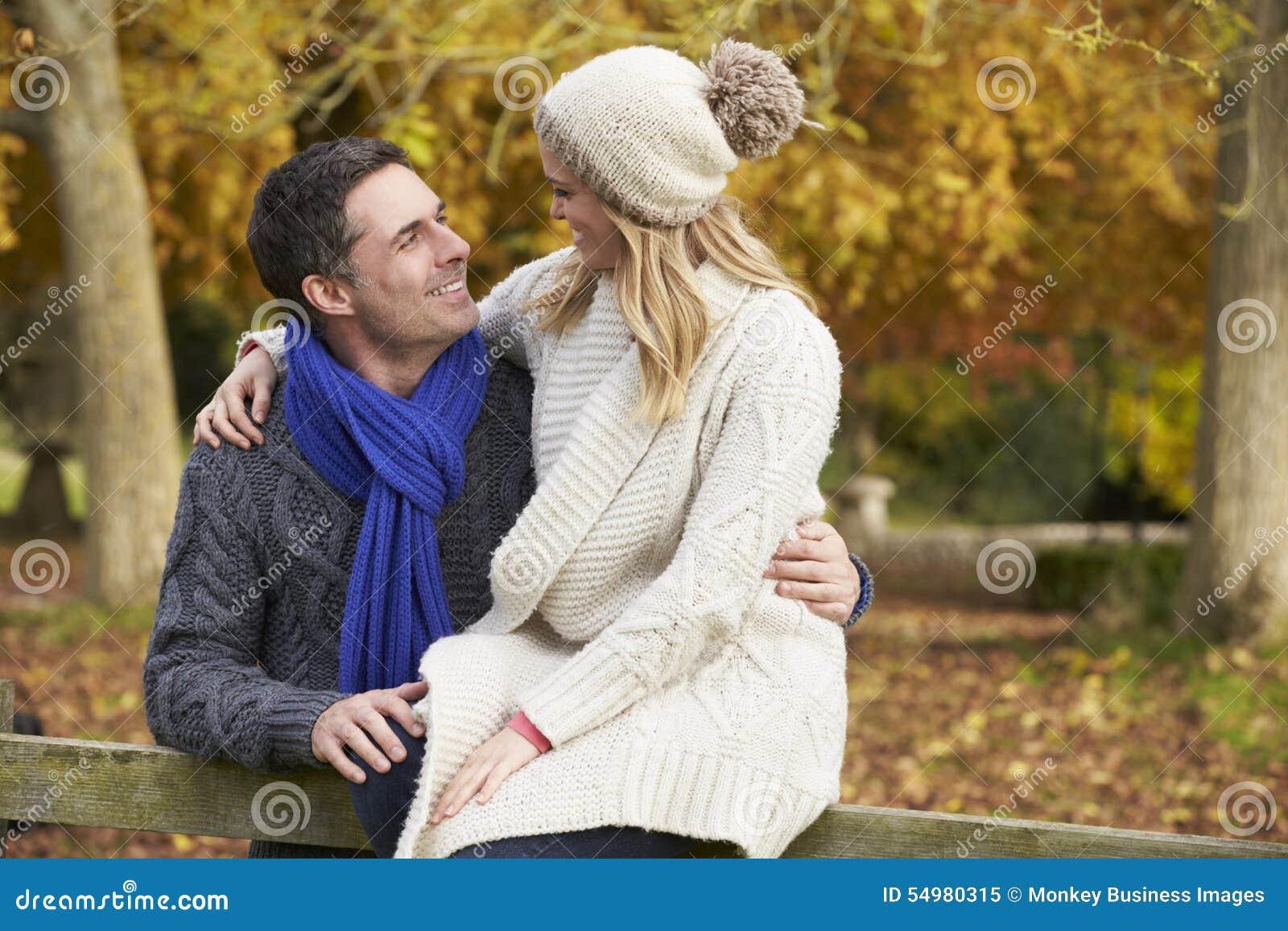 Romantiskt parsammanträde på staketet In Autumn Woodland