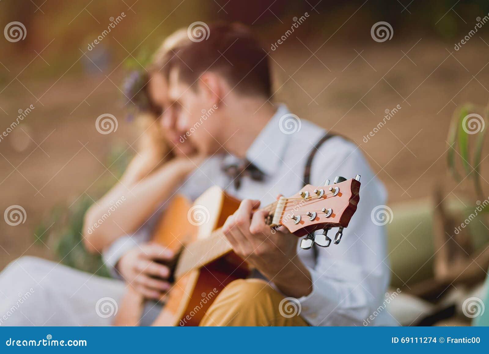 Romantyczna para siedzi outdoors przy zmierzchem z mężczyzna bawić się gitarę