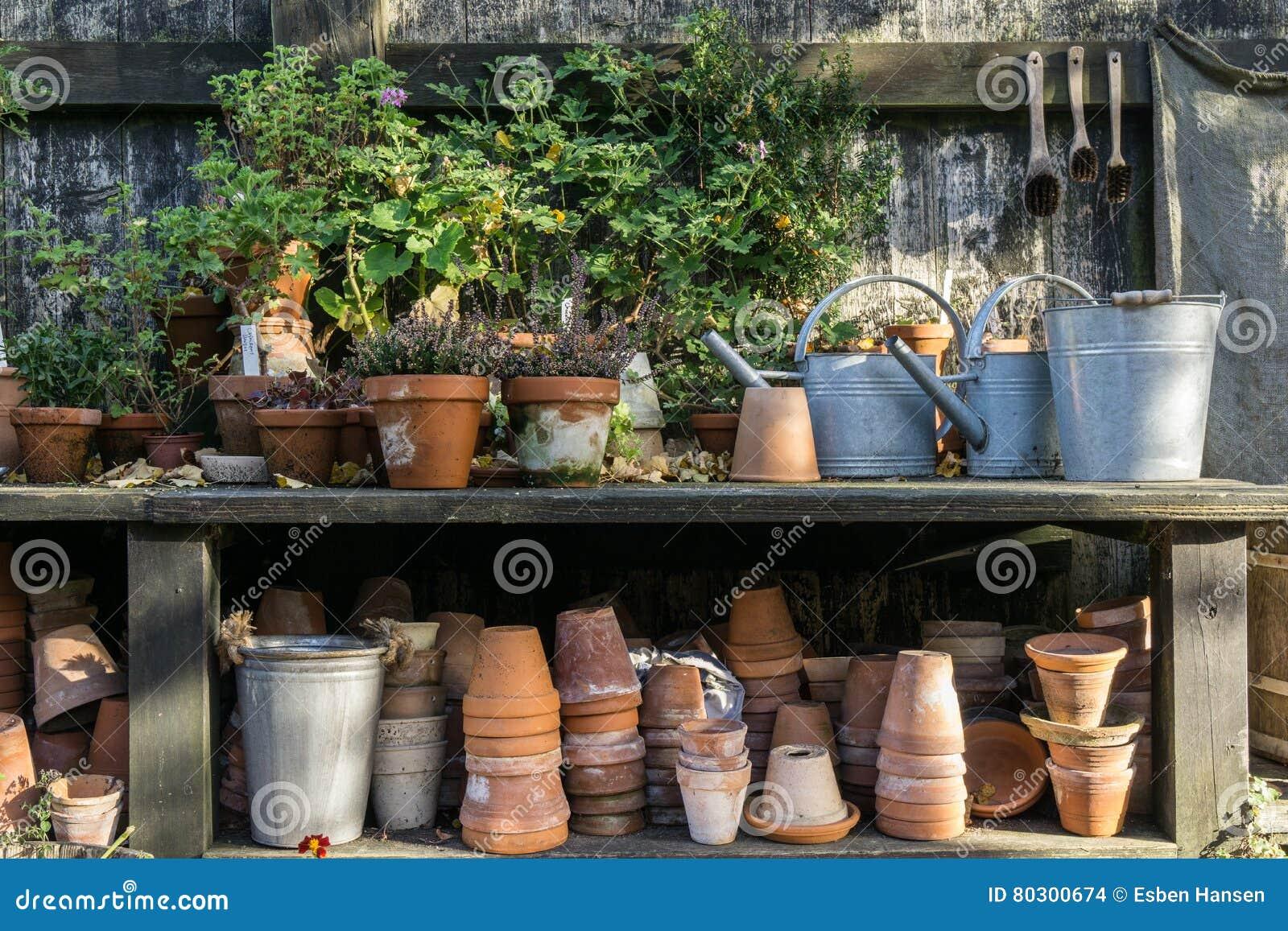 Romantyczny idylliczny roślina stół w ogródzie z starym retro kwiatu garnkiem puszkuje, wytłacza wzory, i rośliny