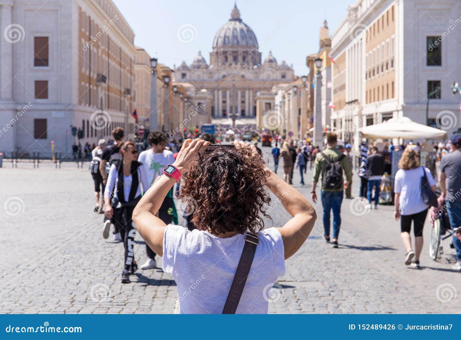 ROME, ITALIË - APRIL 27, 2019: De jonge vrouw fotografeert de Basiliek van Heilige Peter, Rome, Italië