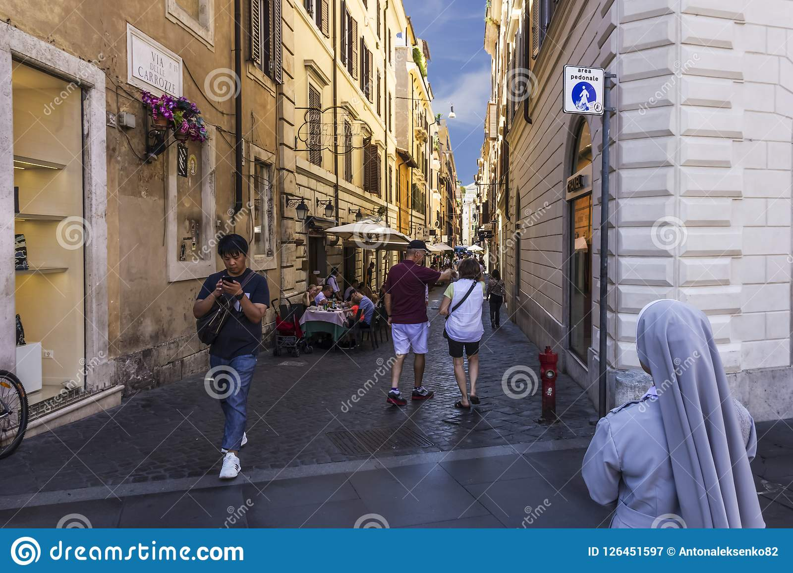 Rome/Italy - August 26, 2018: Italian Street Via Delle Carrozze with tourists, street cafes and a votaress