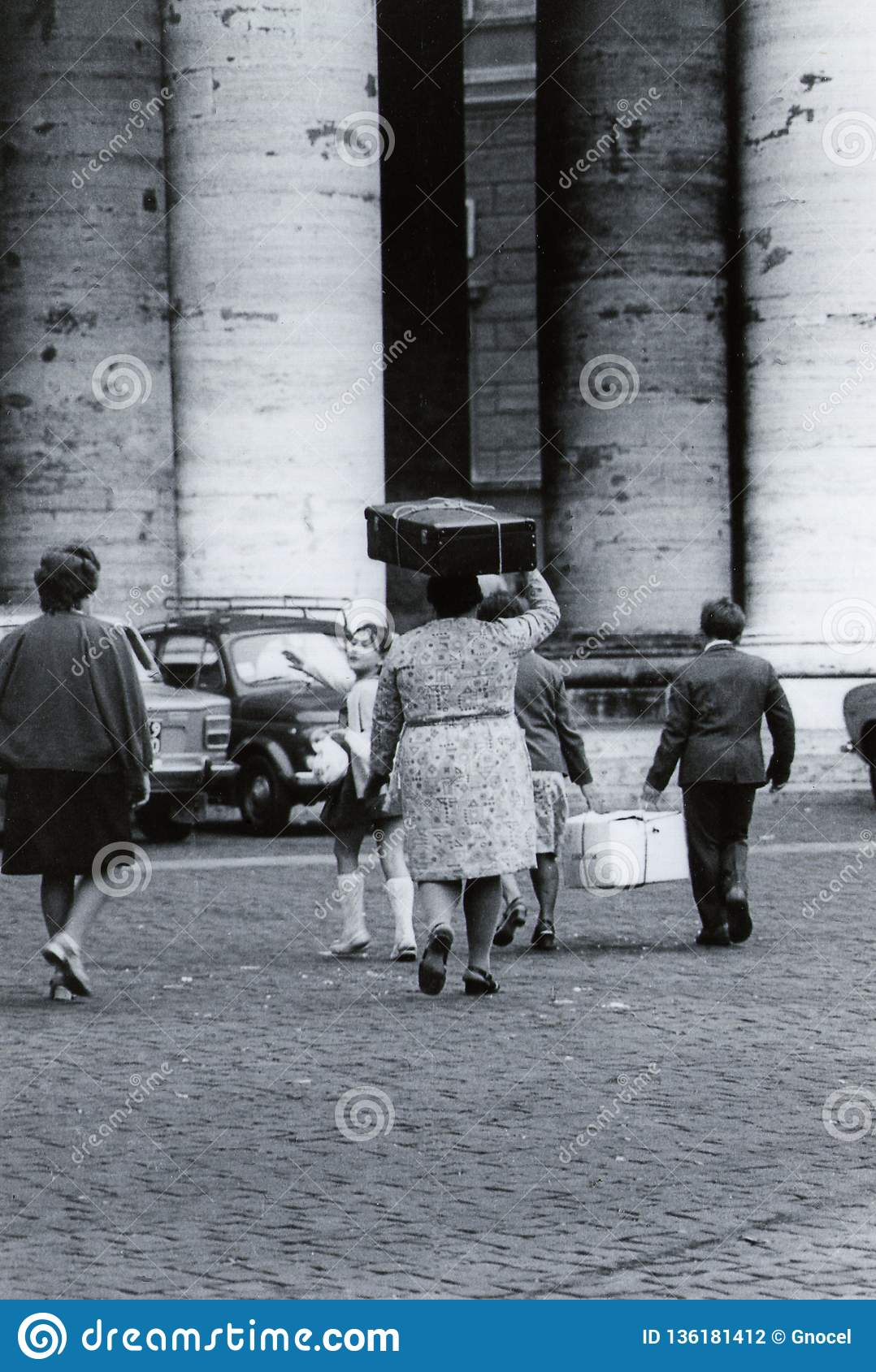 ROME, ITALY, 1970 - A family of emigrants walks near the colonnade of S.Peter Square with a cardboard box and a suitcase on the