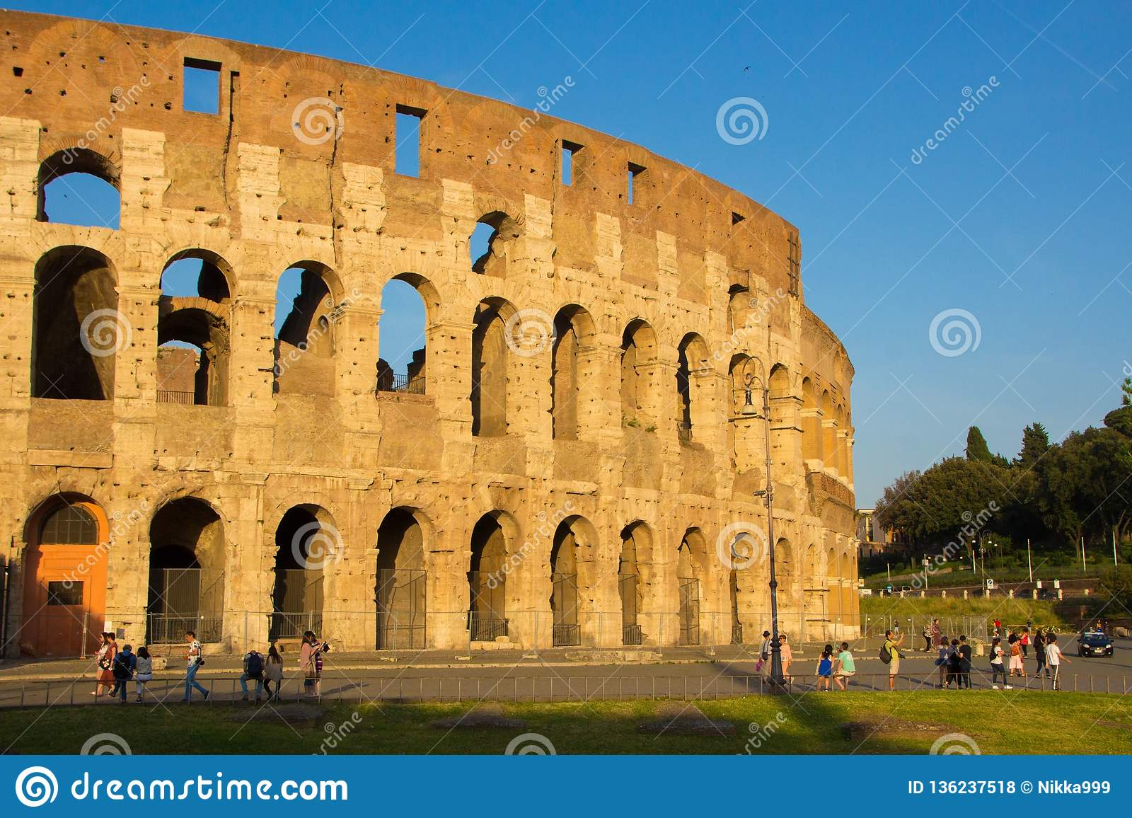 Rome, Italy - May 31, 2018: Roman Colosseum at sunset. Tourists walk near the Colosseum, Golden evening hour. Not restored old