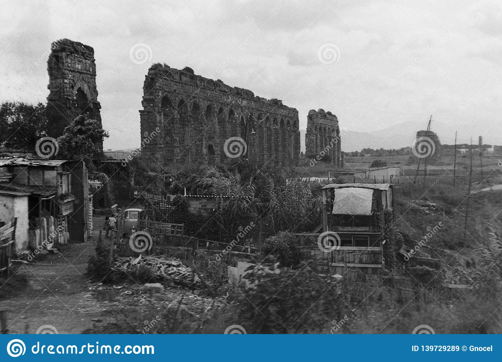 ROME, ITALY, 1966 - The ruins of the Roman aqueduct are home to some poor barracks