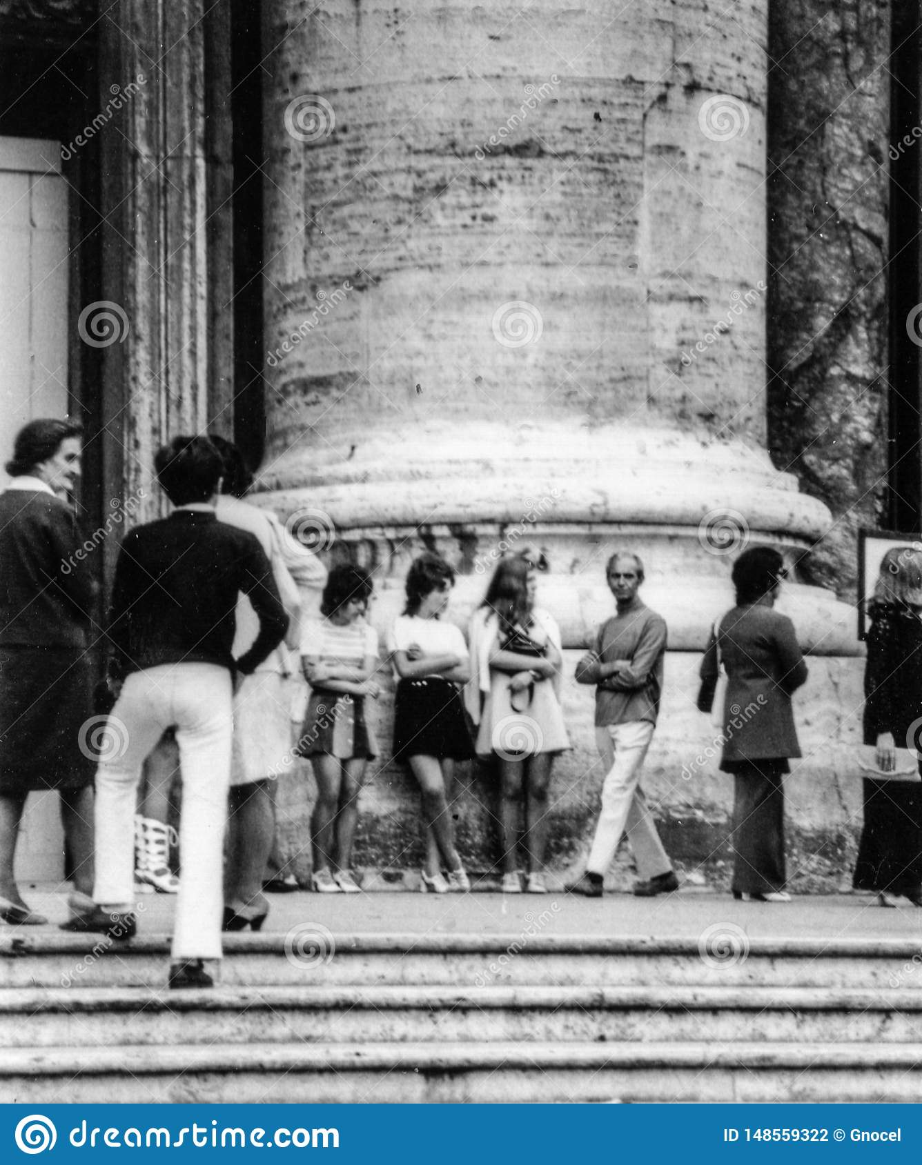 Rome, Italy, 1970 - Three girls in miniskirts rest in the crowd at the foot of a column