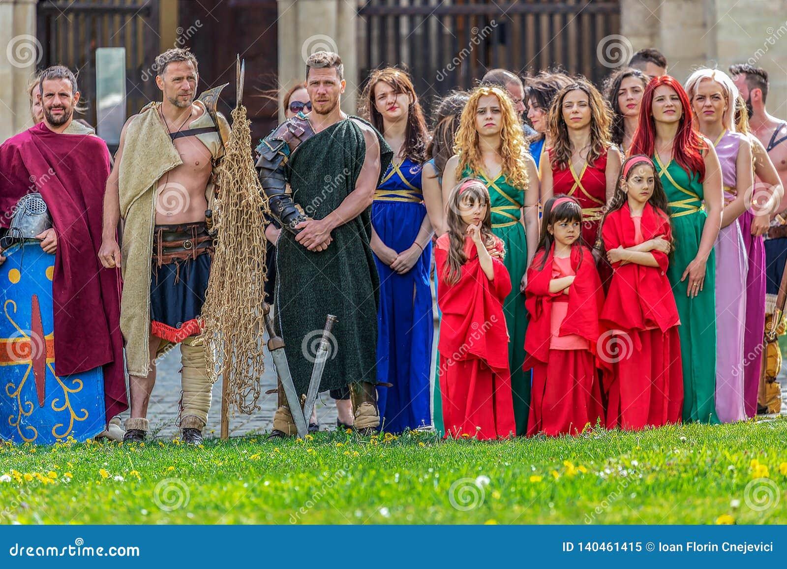 Romersk gladiator i striddräkt och en grupp av unga romerska flickor