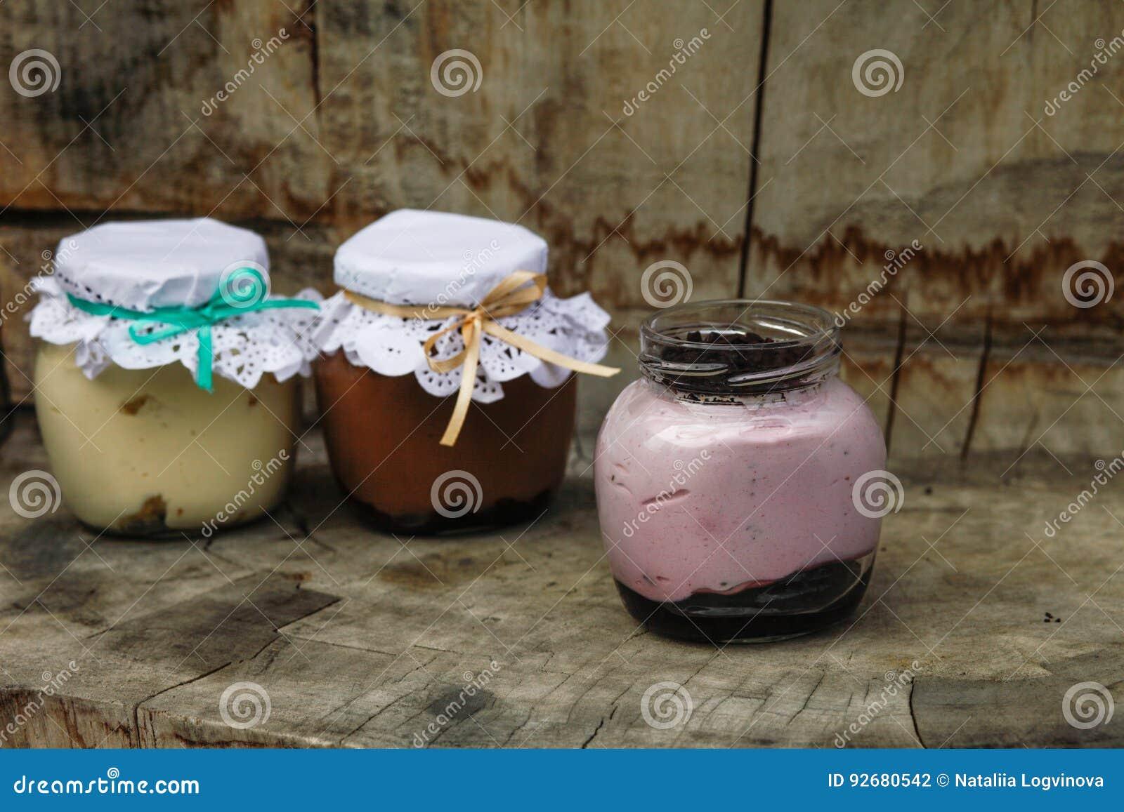 Romig dessert in een kleine glaskruiken met lint op een houten achtergrond