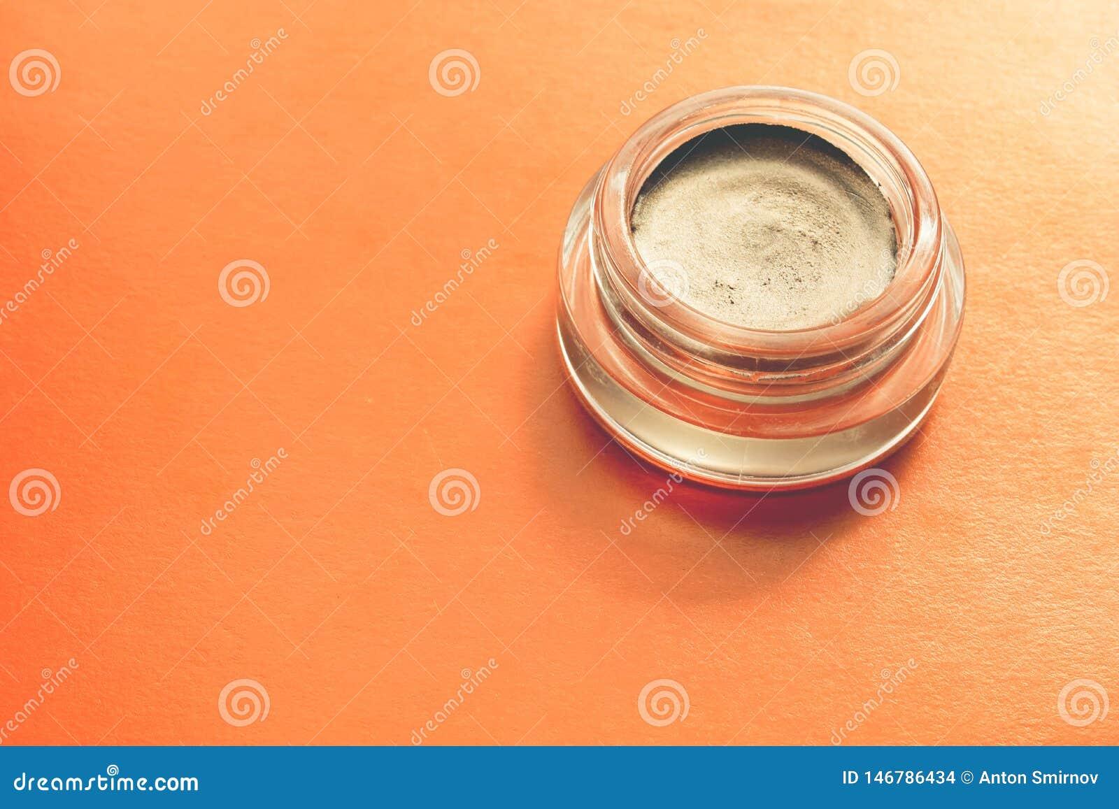 Romige oogschaduw met een metaaleffect in een glaskruik op oranje achtergrond