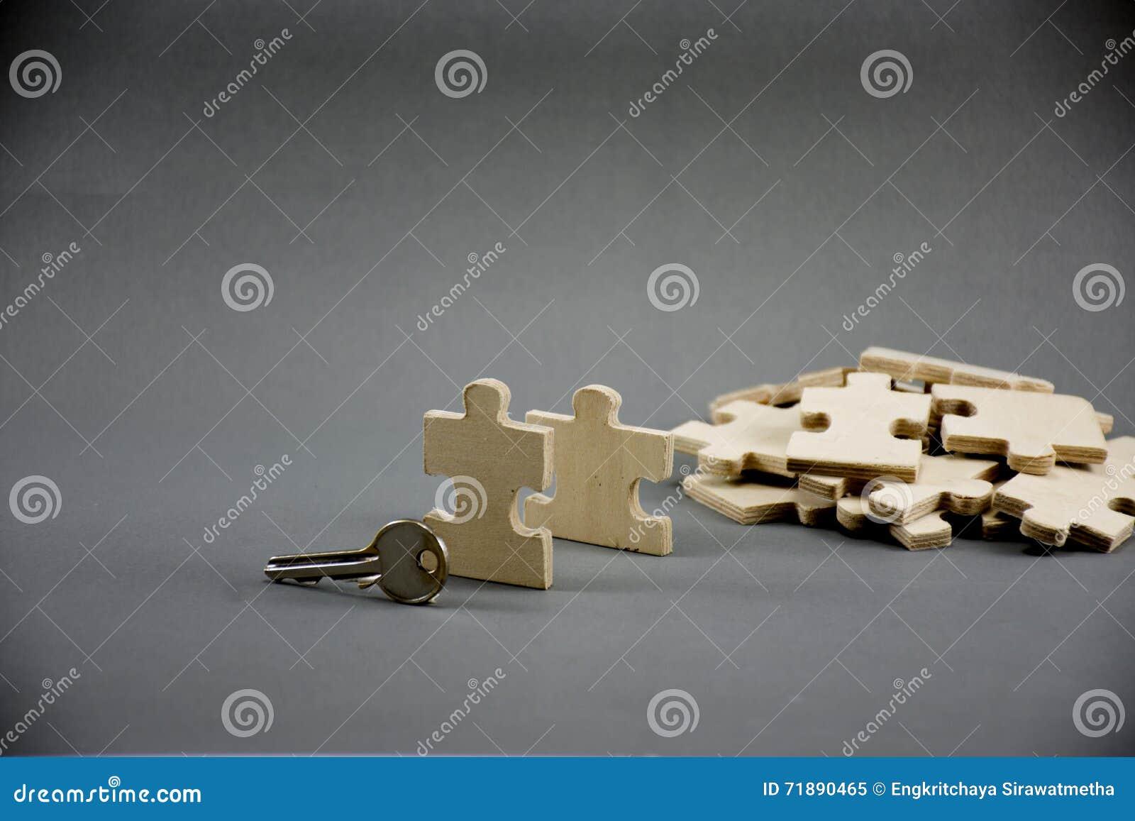 Rompecabezas hecho de la madera con llave en fondo gris con idea del negocio, negocio de MLM o el hombre de negocios Steps al éxi