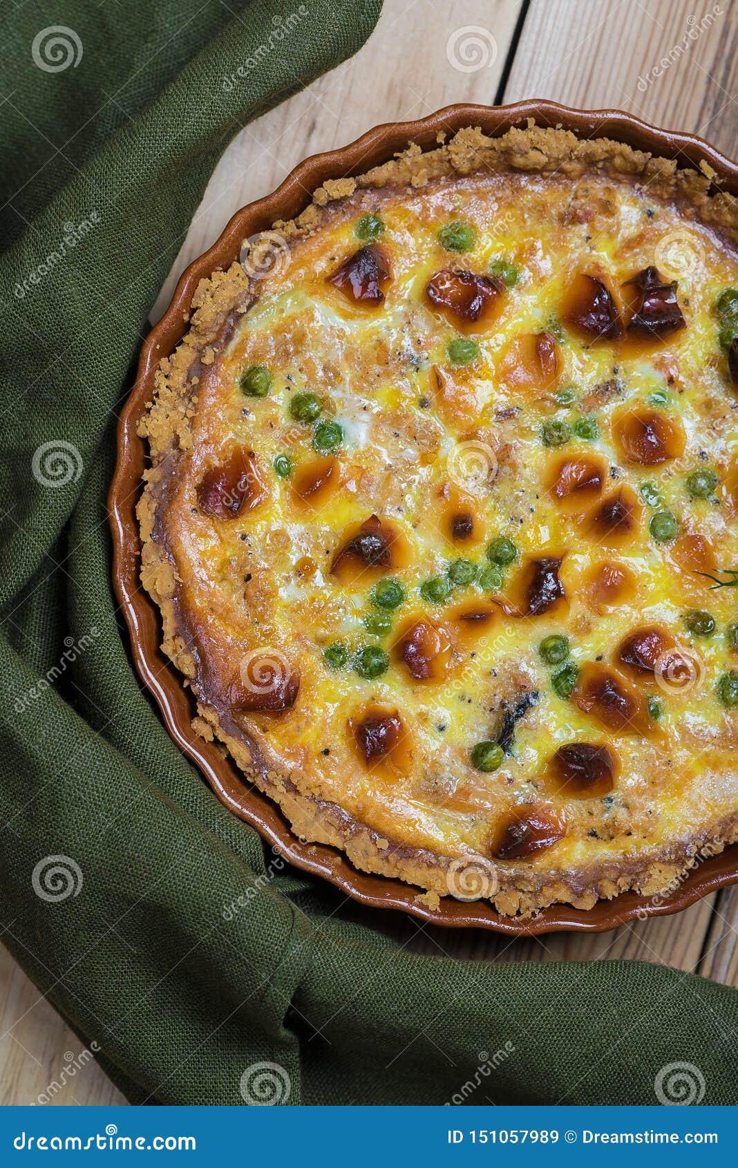 Ronde blozende open pastei met groente en kaas het vullen