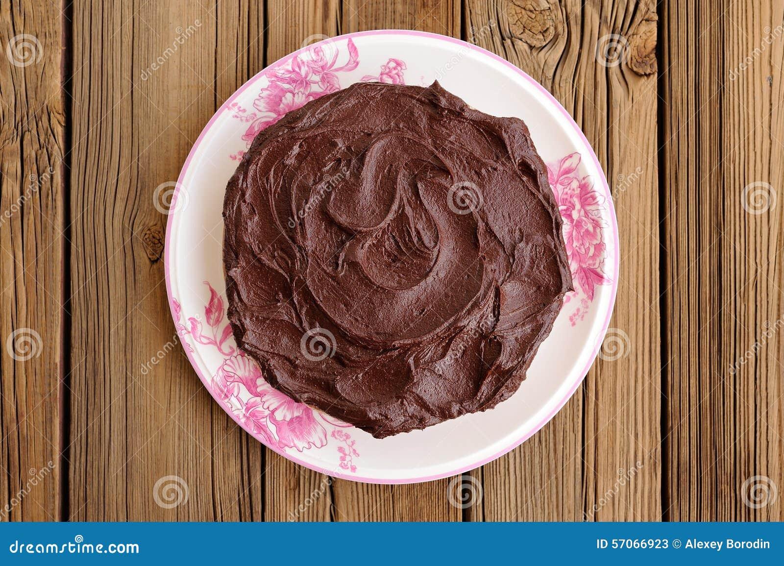 Ronde eigengemaakte die chocoladecake met dikke ganache in whit wordt behandeld