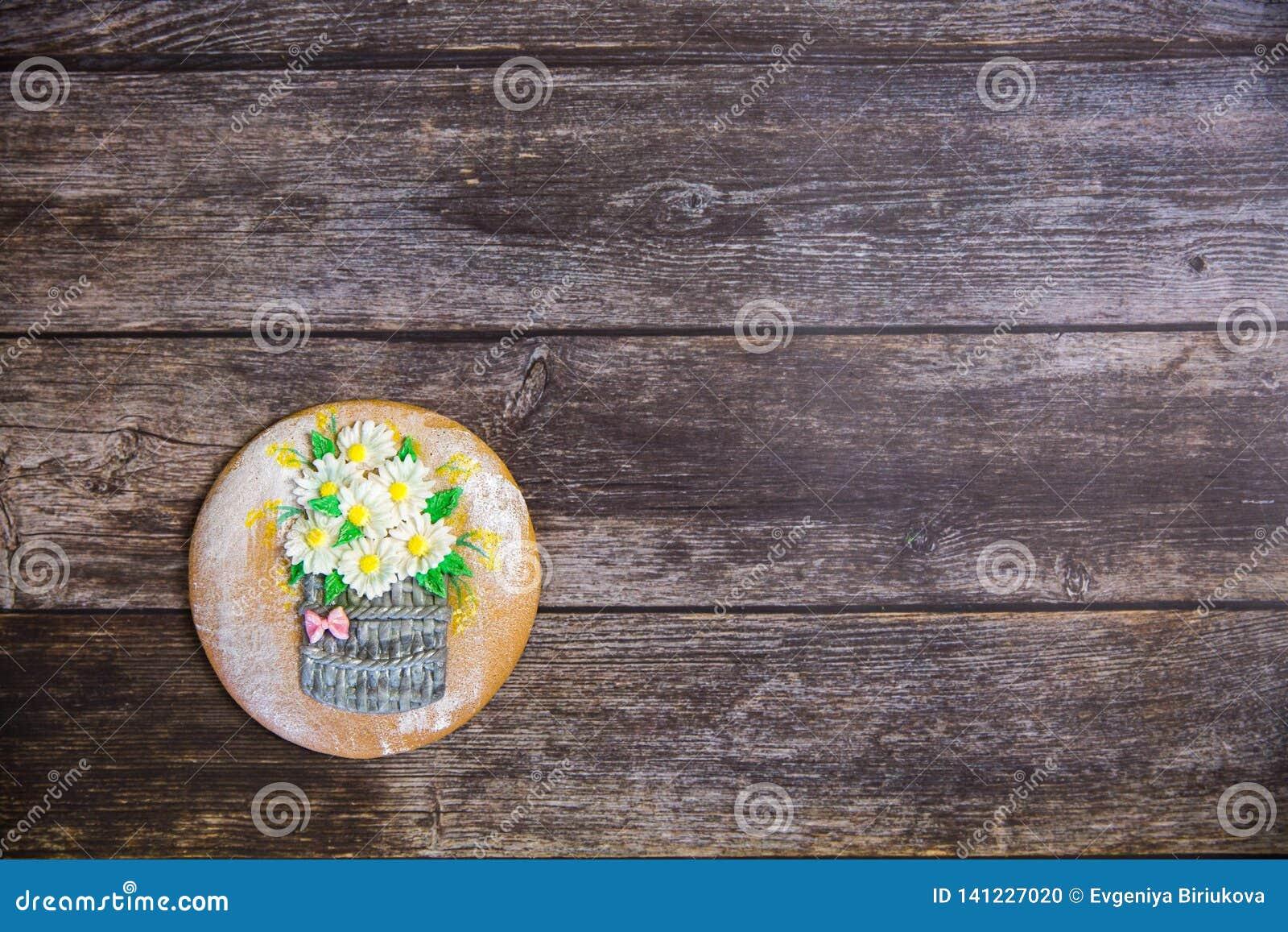 Ronde met de hand geschilderde peperkoek op houten achtergrond Boeket van madeliefjes in een mand Vlak leg De ruimte van het exem