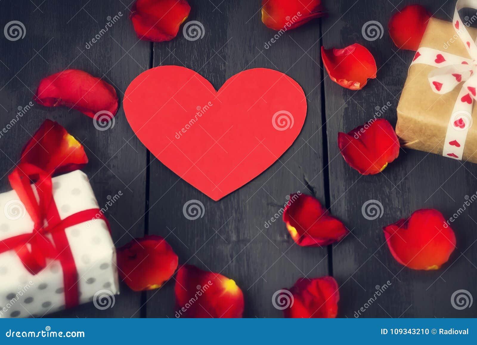 Rood document hart met roze bloemblaadjes en giften op een donkere houten achtergrond St de Dag van de valentijnskaart ` s