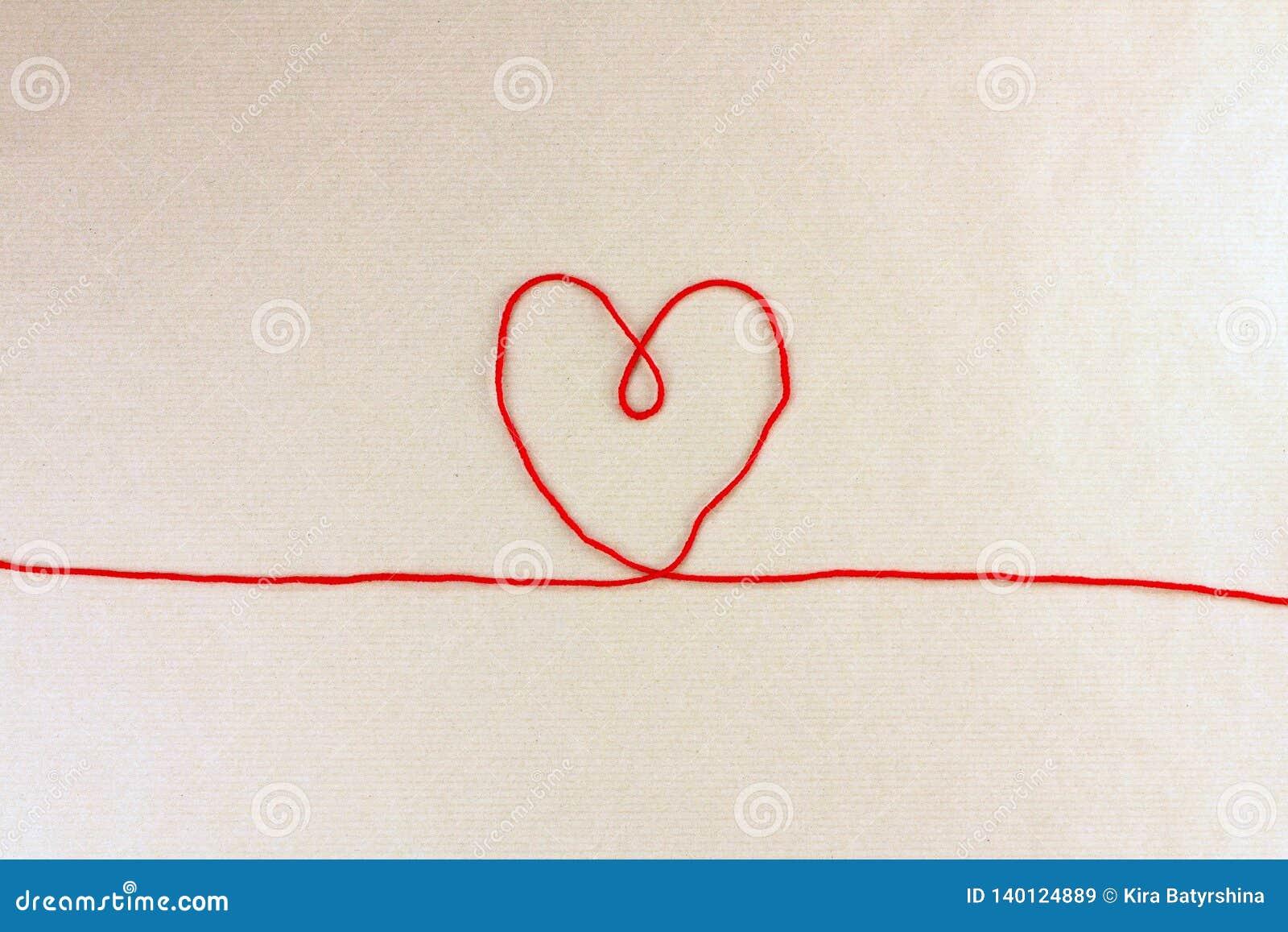 Rood draad, hart en verwarring op lichte ambachtdocument achtergrond, liefdeconcept, hoogste mening
