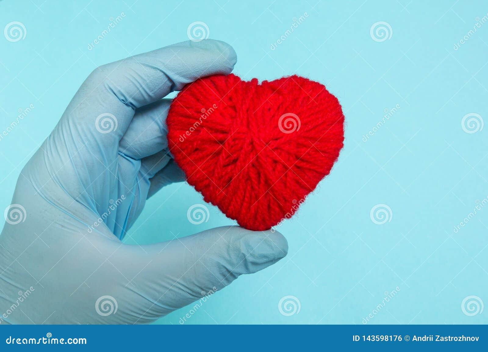 Rood hart in de hand van de arts op een blauwe achtergrond, concept