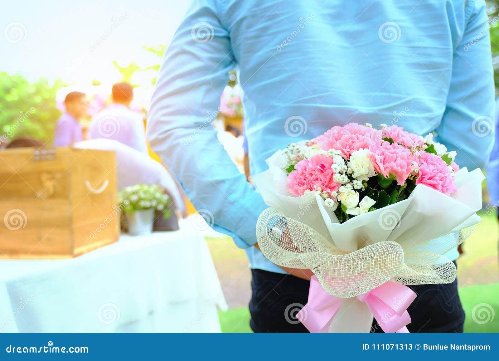 Rood nam toe Mens het verbergen achter een boeket van bloemen knap