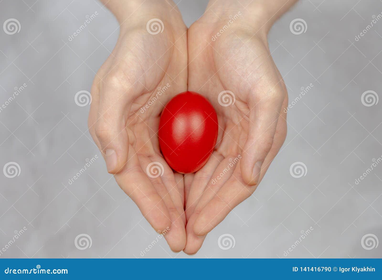 Rood paasei die in zijn palm, een godsdienstig symbool liggen